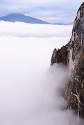 Layers of cloud swirl around the huge cliffs of Monte Brento, Arco, Italy