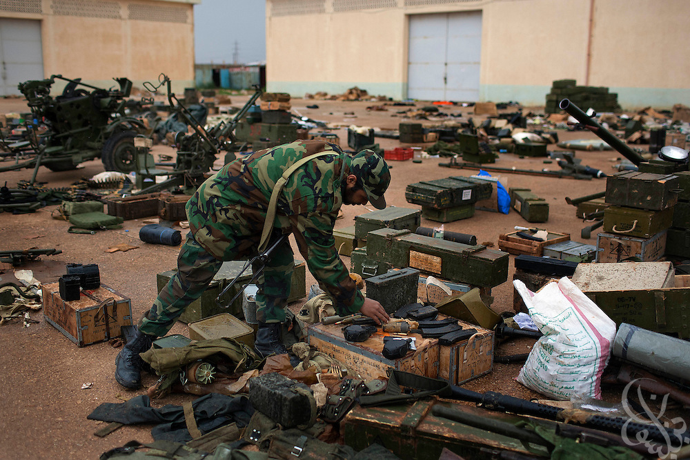 A unit of defected paratroopers takes stock of looted weapons, including guns, grenades, mines, rockets and missiles that they have re-collected from civilians at their base February 26, 2011in Benghazi, Libya. There are unconfirmed reports a rebel force, made up of defected soldiers and volunteers,  is moving closer to the capital Tripoli..Slug: Libya.Credit: Scott Nelson for the New York Times