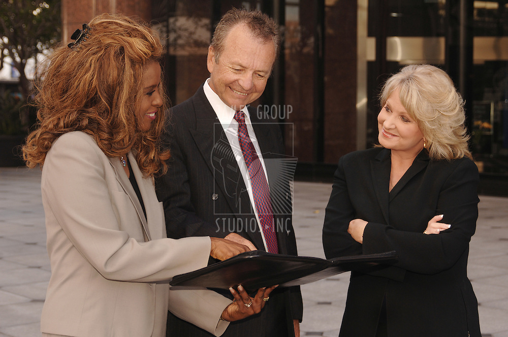 Two professional women and one businessman confer outside an office building