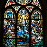 A stained glass window at St. Mary Church in Luxemburg, Wis., depicts the Holy Spirit descending upon the apostles at Pentecost. (Sam Lucero | The Compass)