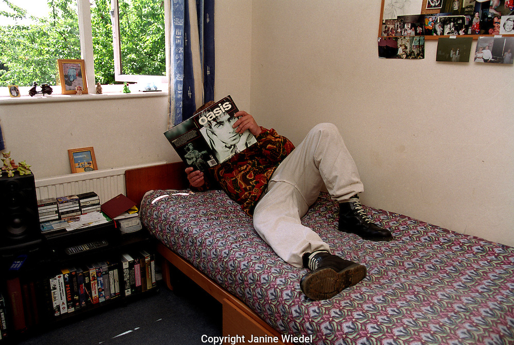 Young offender resting on his bed in a hostel.