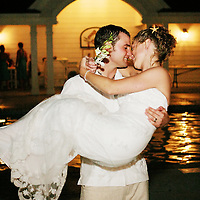 Groom carrying bride while kissing
