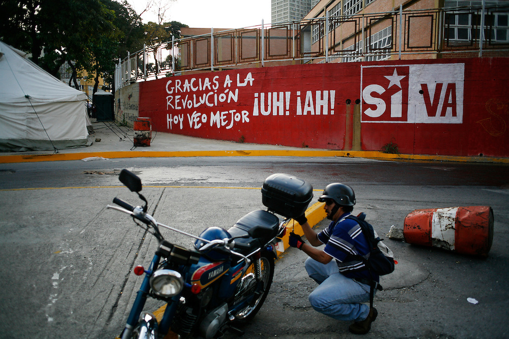 A man fixes his motorcycle in front of a painting in support of Chavez in Caracas. Motorcycles are the ride of choice for many Caracas residents. Bacause of the amount of traffic, the motorcycles are often much faster since they weave in between cars. However, they can be extremely dangerous and most recently motorcycle taxi drivers are fighting for their rights after a number of them have been killed while being robbed for their motorcycle.