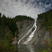Otter Falls races down relatively smooth granite into Lipsy Lake. No otters live here; the falls were presumably named for the fact that otters might enjoy the natural slide. Otter Falls is estimated at 1,600 feet tall, though only the bottom few hundred feet are visible here. The falls, located east of North Bend, Washington in the Mount Baker Snoqualmie National Forest, is typically dry by mid-summer.