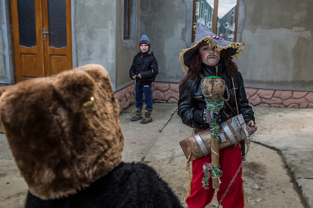 Boys, dressed as a bear and a gypsy, respectively, perform ritual songs and skits of the Malanka Festival on Wednesday, January 13, 2016 in Krasnoilsk, Ukraine. The festival doesn't officially begin until sundown.