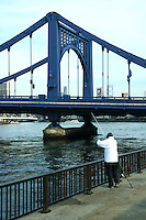 "Japanese fisherman along the banks of the Sumida River by Kiyosubashi Bridge.  The Kiyosu Bridge, built in 1928 after the model of the Deutz Suspension Bridge of Cologne, links Kiyosu with Nihonbashi. The Sumida River or Sumida-gawa as it is known in Japanese, is a river which flowing through Tokyo. It branches from the Arakawa River and flows into Tokyo Bay. Its tributaries include the Kanda and Shakujii rivers. What is now known as the ""Sumida River"" was previously the path of the Arakawa River, however towards the end of the Meiji period the rivers were diverted from the main flow of the Arakawa to prevent flooding."