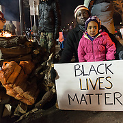 Ibrahim Kamia of Minneapolis, with his daughter Yeleen, 3, drove a minivan full of wood from his backyard to donate for fires to warm Black Lives Matter protesters as people gathered for a night of community and protest outside the Minneapolis Police Department 4th precinct headquarters on Thursday, November 19, 2015 in Minneapolis, Minnesota. He said he wanted his daughter to see the scene. <br /> <br /> A more mellow and festive atmosphere, with a smaller police presence, prevailed after Wednesday evening's tear gas clashes between police and protesters. <br /> <br /> Protests and an encampment at the site have been ongoing since the police shooting of 24-year-old Jamar Clark by Minneapolis Police on Sunday, November 15. <br /> <br /> <br /> Photo by Angela Jimenez for Minnesota Public Radio www.angelajimenezphotography.com