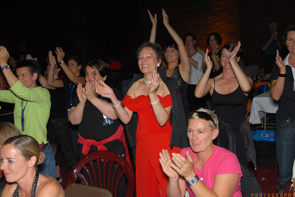 """Spectators and fellow same-sex dancers cheer as the announcement is made that Jazz Munteanu and Karin Stjarnefyr (umlaut on the """"a""""), both of Sweden, (not shown in photo) have won the A category adult women's latin division championship of the same-sex ballroom dancing competition during the 2007 Eurogames at the Waagnatie hangar in Antwerp, Belgium on July 13, 2007. ..Over 3,000 LGBT athletes competed in 11 sports, including same-sex dance, during the 11th annual European gay sporting event. Same-sex ballroom is a growing sports that has been happening in Europe for over two decades."""