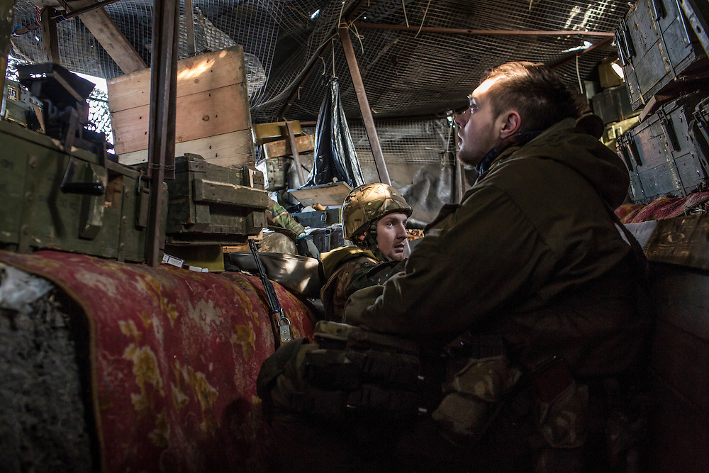 PISKY, UKRAINE - MARCH 20, 2015: Fighters for the Dnipro-1 battalion, a pro-Ukrainian militia, sit in a front-line trench in Pisky, Ukraine. CREDIT: Brendan Hoffman for The New York Times
