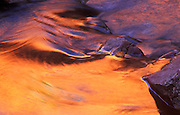 Image of water detail with soft sunset reflection in ripple