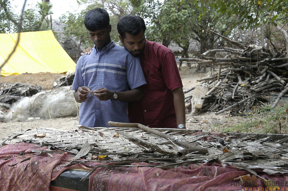 Hari N., 22, right, a volunteer with AID India from Bangalore, comforts Prakash M., 20, left, a young fisherman, among the wreckage of his family's home in the fishing village of Perumalpettai in Tamil Nadu, India, on January 21, 2005. Prakash lost his home and his mother to the Indian Ocean Tsunami on December 26, 2004. Generated by an earthquake on the ocean floor, the tsunami devastated the fishing industry along the southeastern coast of India.