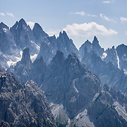 """Sharp peaks of the Cadini Group rise in the Sesto Dolomites, Veneto region, Italy, Europe. In the Cadini di Misurina, Cima Grande rises to 2999 meters (9839 feet), between Cima Piccola and Cima Ovest. The Cadini Group is in the municipality of Auronzo, in the Sesto Dolomites (Dolomiti di Sesto, or Sexten/Sextner/Sextener Dolomiten) which lie north of the Fiume Ansiei valley. From the Rifugio Auronzo toll road, hike for spectacular views around Tre Cime di Lavaredo (Italian for """"Three Peaks of Lavaredo,"""" called Drei Zinnen or """"Three Merlons"""" in German). The Dolomites are part of the Southern Limestone Alps. UNESCO honored the Dolomites as a natural World Heritage Site in 2009."""