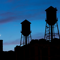 USA, New Jersey, Jersey City, Rooftop water towers and setting crescent moon