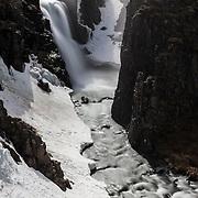 A long exposure blurs the water flowing over Fardagafoss, a waterfall near Egilsstaðir, Iceland.