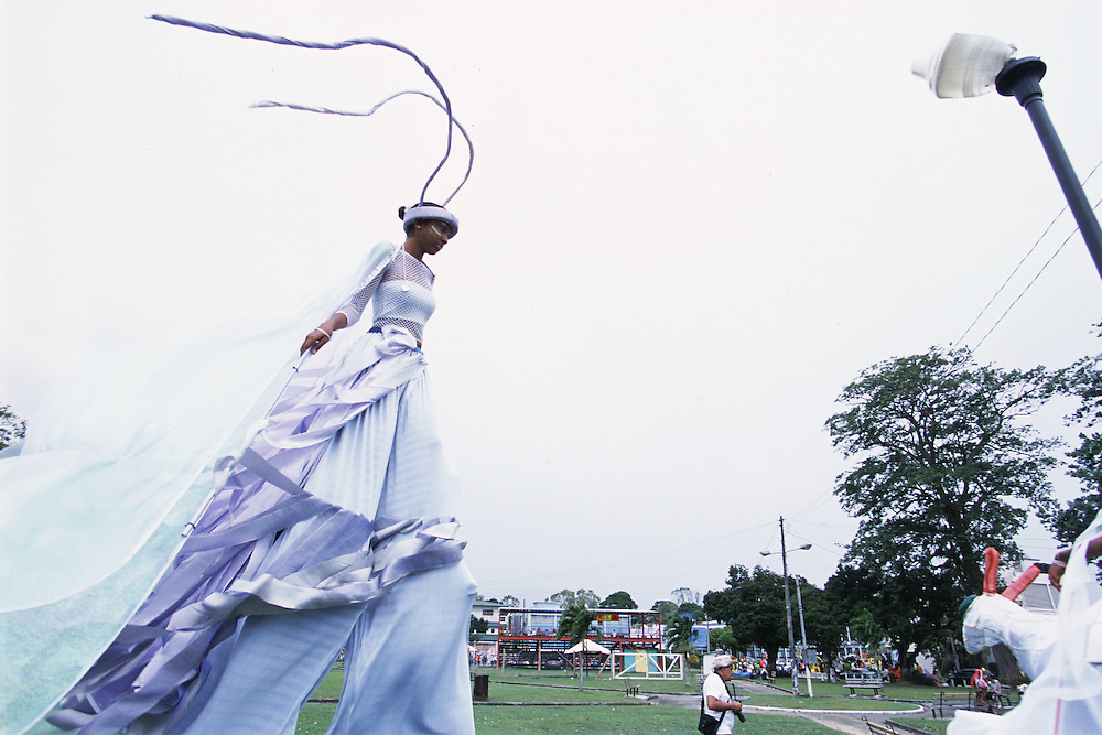 """Trinidad and Tobago """"MOKO JUMBIES: The Dancing Spirits of Trinidad"""".(At Adam Smith Square, where she will take part in the Junior Individual competition, Ria Walters strolls by  in the """"Batimamselle"""" costume, designed by Laura Anderson Barbata. She won first place.).A photo essay about a stilt walking school in Cocorite, Trinidad..Dragon Glen de Souza founded the Keylemanjahro School of Art & Culture in 1986. The main purpose of the school is to keep children off the streets and away from drugs..He first taught dances like the Calypso, African dance and the jig with his former partner Cathy Ann Samuel.  Searching for other activities to engage the children in, he rediscovered the art of stilt-walking, a tradition known in West Africa as the Moko Jumbies , protectors of the villages and participants in religious ceremonies. The art was brought to Trinidad by the slave trade and soon forgotten..Today Dragon's school has over 100 members from age 4 and up..His 2 year old son Mutawakkil is probably the youngest Moko Jumbie ever. The stilts are made by Dragon and his students and can be as high as 12-15 feet. The children show their artistic talents mostly at the annual Carnival, which today is unthinkable without the presence of the Moko Jumbies. A band can have up to 80 children on stilts and they have won many of the prestigious prizes and trophies that are awarded by the National Carnival Commission. Designers like  Peter Minshall , Brian Mac Farlane and Laura Anderson Barbata create dazzling costumes for the school which are admired by thousands of  spectators. Besides stilt-walking the children learn the limbo dance, drumming, fire blowing and how to ride  unicycles..The school is situated in Cocorite, a suburb of Port of Spain, the capital of Trinidad and Tobago..all images © Stefan Falke"""