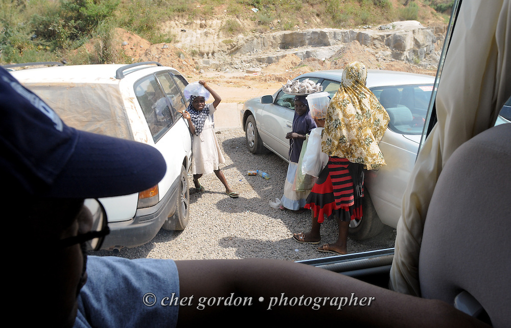 Young Nigerian girls sell water and nuts to motorists in a parking lot at Nnamdi Azikiwe International Airport in Abuja, Nigeria on Sunday, December 2, 2012.
