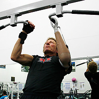 Bob Radocy of TRS Inc. uses a grip prehensor hand replacement to do pull-ups at a gym in Boulder, Colorado August 21, 2009. Radocy designs and builds prosthetic attachments that allow amputee athletes to participate in multiple sports.  REUTERS/Rick Wilking (UNITED STATES)