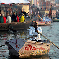Asia, India, Varanasi. A man rows on the Ganges River in Varanasi.