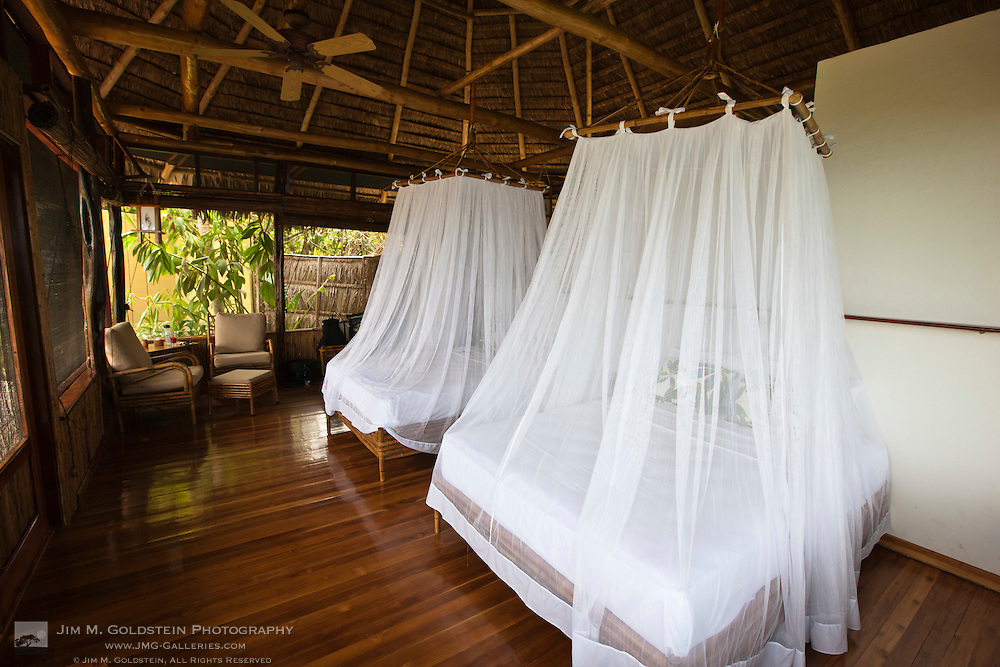 Interior view of mosquito net covered beds in a luxurious ecolodge bungalow in the lower Osa Peninsula of Costa Rica