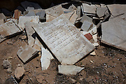 Brocken  marble tombstones that litter the outer perimeter of the cemetery behind the Great Synagogue of the tiny Tunisian Jewish community on the island of Djerba on May 27,2016. Vandals  did not break the gravestones he said but instead the graves were exhumed and sent to Israel for reburial . (Photo by Heidi Levine).