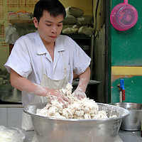 Asia, China, Chongqing. Chinese vendor kneads dough by hand in street market in Chongqing.