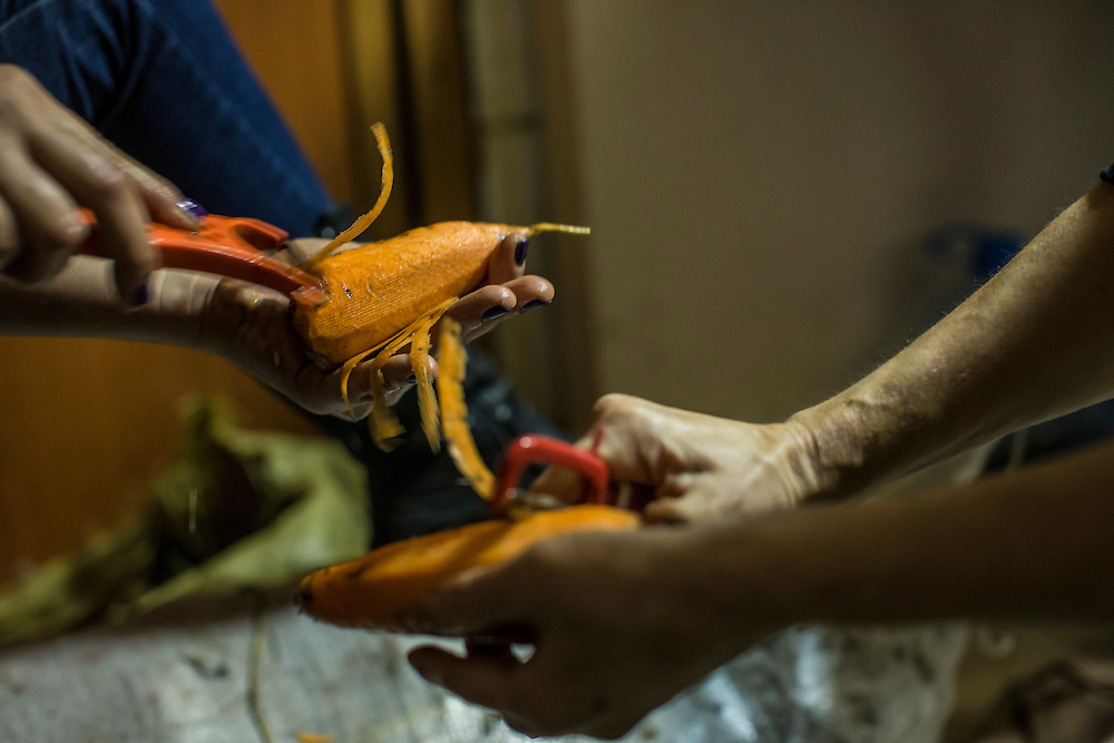 DNIPROPETROVSK, UKRAINE - NOVEMBER 16, 2014:  Zhanna Kuzmytska, 23, a psychologist, left, and Natalia Nechukhayeva, 55, a teacher, peel carrots for soup at the Dnipropetrovsk Volunteer Logistics Center, a charity organization that produces supplies for pro-Ukrainian fighters battling rebels in the country's East, in Dnipropetrovsk, Ukraine. CREDIT: Brendan Hoffman for The New York Times