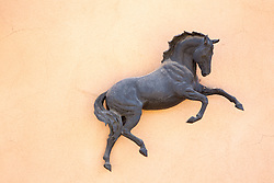 bronze sculpture of a horse on a wall