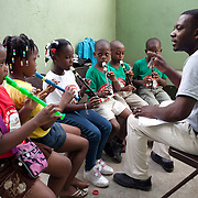 Instructor Jetho Benoit, a former student, teaches recorder to a group of young children in the wind instruments building.