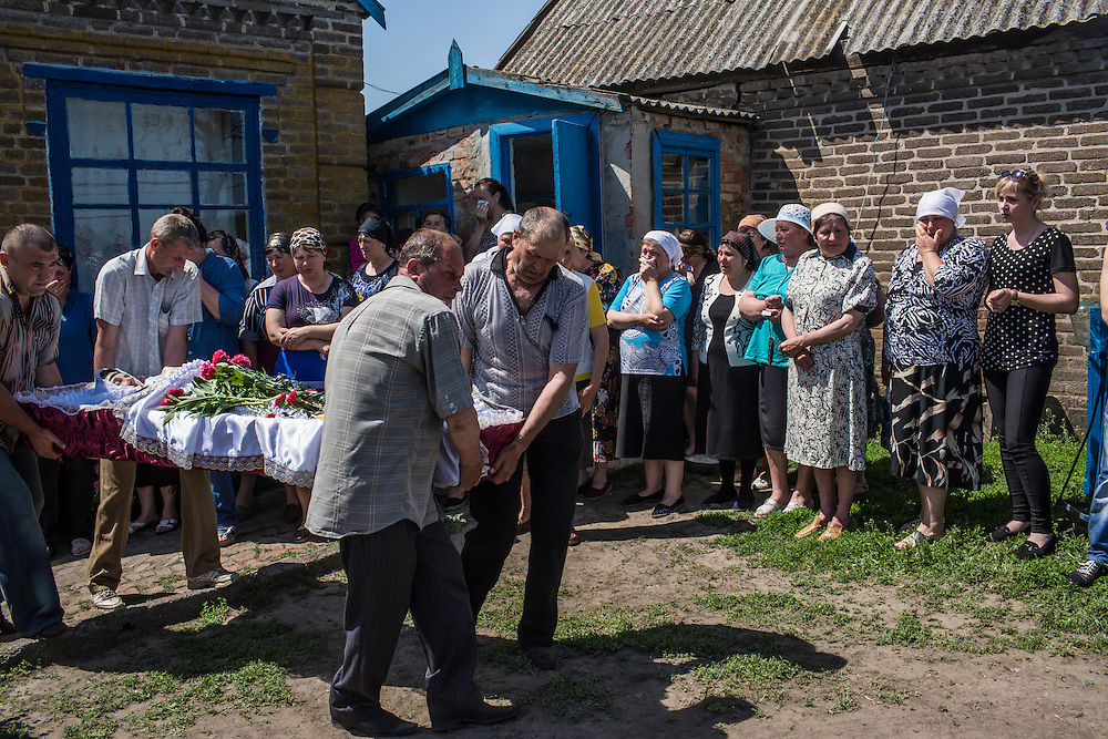 STAROVARVAROVKA, UKRAINE - MAY 16:  The casket of Elena Ott, 42, is carried out of her family's house on May 16, 2014 in Starovarvarovka, Ukraine. Ott was killed two days prior when the car she was riding in was fired on by forces her family believes to be the Ukrainian military. (Photo by Brendan Hoffman/Getty Images) *** Local Caption ***