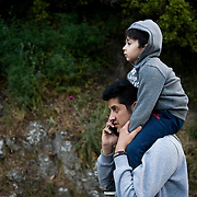 An Afghan carrying his child is walking the the 9 hour distance from Skala Sykaminias to the village of Moria where the First Reception Centre is located. Everyday hundreds of refugees, mainly from Syria and Afghanistan, are crossing in small overcrowded inflatable boats the 6 mile channel from the Turkish coast to the island of Lesbos in Greece.