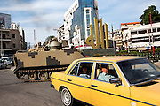 """A Lebanese army tank manoeuvres through a roundabout in which a gold Arabic sign stands which reads, """"Allah,"""" in the northern city of Tripoli, Lebanon. Tripoli has seen a rise in extremist elements over the past few years with Salafists playing an increased military role there."""
