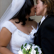 Hispanic lesbian couple bride and groom kissing, before the start of the Pride Parade.  New York State became the 6 state to make gay and lesbian marriages legal starting  July 1, 2011.  Couple dressed as bride and groom are planing to marry in July. Gender and sexual orientation and sexual identity.