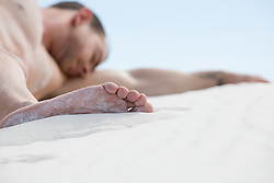 detail of a man sleeping on sand