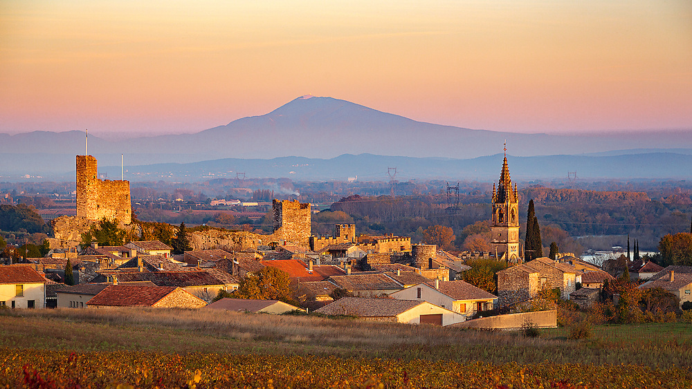 """Sunset over Aigueze with Mont Sainte Victoire in the distance. Aiguèze is a commune in the Gard department in southern France. Since 2005, Aiguèze has been a member of Les Plus Beaux Villages de France (""""The most beautiful villages of France""""), the first such location in Gard."""