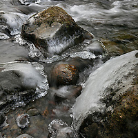 WA08996-00...WASHINGTON - Ice rimed rocks in the South Fork Snoqualmie River near Olallie State Park.