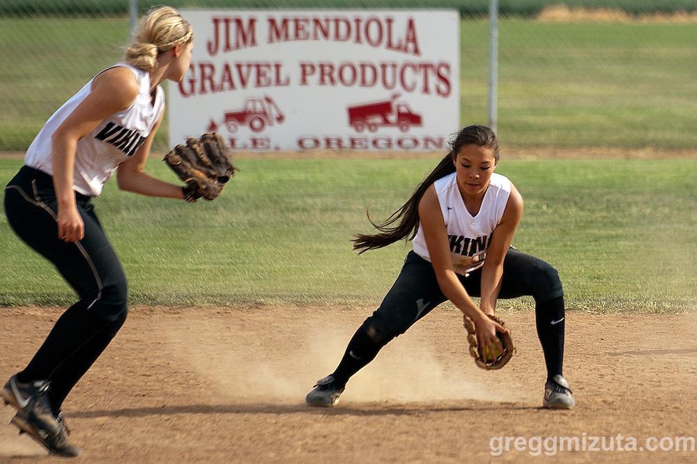 Vale sophomore shortstop Hannah Mizuta fields a ball as third baseman Kiara Cooper looks on during the Vale-Nyssa doubleheader at Vale High School, Vale, Oregon, May 8, 2015.