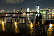 A couple looks at Rainbow Bridge, which connects downtown Tokyo with Odaiba island across Tokyo Bay.