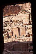 Tombs of the Street of Facades framed by a carved doorway in Petra, Jordan.