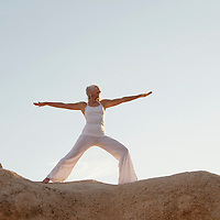 Mature woman in warrior 2 yoga pose on the rocks.<br /> &ldquo;Almost all action is based at its root on a spiritual impulse . . . That is, a desire to experience a lightness of being and transcendence that does not take us away from our everyday experience but exists within it.&rdquo;<br /> <br /> Donna Farhi : Bringing Yoga to Life