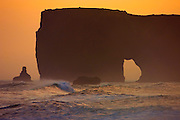 The Lundadrangur Rock Arch towers high above the Atlantic Ocean at Dyrhólaey, Iceland. The Dyrhólaey Cliffs, which stand 120 meters (394 feet), were formed during an underwater volcanic eruption during the last ice age.