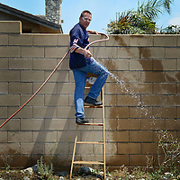 Rick Pollack, a homeowner in the  the Etiwanda Estates subdivision in Rancho Cucamonga, uses a hose to put out spot fires in weeds near his home Wednesday as the Etiwanda Fire burns nearby. Pollack and others had ignored a mandatory evacuation order and stayed behind to defend their homes. <br /> <br /> <br /> Rancho Cucamonga, CA: The Etiwanda Fire raced through the foothills of Rancho Cucamonga Wednesday April 30, 2014 near Los Angeles CA. The fire had consumed hundreds of acres by mid afternoon and hundreds of homes were evacuated. <br /> <br /> Fire size estimate as of 2:50 p.m. is 800 acres.