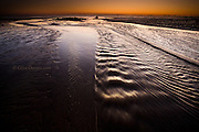Low tide at sunset at Cymyran beach near Rhosneigr. A beautiful but quiet  windswept beach on Anglesey's West coast. At low tide the sea always creates amazing patterns and ripples in the sand, interspersed with rivulets and streams from the inland sea.