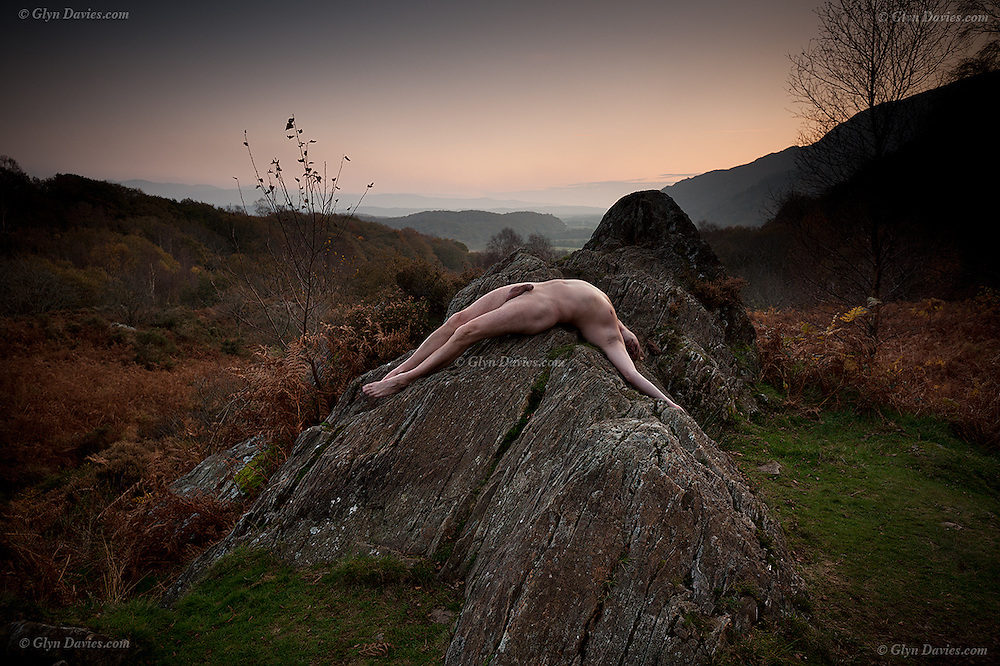 Nominated in 10th (2017) International Colour Awards (Nude category) <br /> <br /> &ldquo;It was dusk and a gentle mist hung in the valleys, illuminated only by the last glimmer of Autumnal daylight. There was delicate moisture in the air and a slight dampness on the short grass surrounding the rock. Rich, earthy smells surrounded me, from the bracken and ancient woodland adjacent to the outcrop. Above the sound of a gurgling brook I could hear a thrush singing somewhere in the distance. Apart from that there was relative silence; no cars, no planes, no groups of chatty &lsquo;ramblers on a mission&rsquo;, just me in what felt like a lost valley. I was alone and had found perfect solitude. <br /> <br /> I enjoyed the feeling of the cool, almost prickly, sheep-mown grass on the soles of my feet, but the rock was warm having basked during a day of unbroken sunshine under clear blue skies.  Although the rocky outcrop looked smooth from a distance it was rough beneath my skin, making my body feel vulnerable to its sharp surface. I enjoyed the sensation nevertheless, feeling utterly and intimately connected to &lsquo;my&rsquo; rock, a rock carved by glaciers millions of years ago, scratched and smoothed by the weight of ice, but today it was just me, an insignificant speck on the planet. Yet the planet means everything to me; I feel it, see it, and hear it. It provides for me, nourishes me and I am a part of it nevertheless. <br /> <br /> As the melody of the Song Thrush drifted away, I lay relaxed, supine, as much of my skin surface in contact with the rock as I could manage, facing the darkening universe above. The rock supported me, it seemed as if the Earth itself was carrying me, a fragile, perishable organic figure, exposed to the air and the elements but wonderfully connected to the land&quot;<br /> <br /> This is a snip from the original article which can be read here: http://www.glynsblog.com/2015/09/then-came-autumn-double-page-spread-in.html