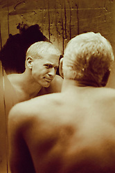 bleach blond man in a bathroom mirror