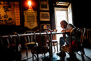 One of the few old-timers left from the Jones and Laughlin mill that used to surround West Aliquippa, Gino DiNardo, reads the paper in Mahoney's West in West Aliquippa, Pennsylvania, USA on May 7, 2015. Mahoneys has been in operation in West Aliquippa for 40 years.