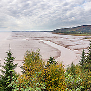 Tidal flats, Hopewell Cape, New Brunswick, Canada. Hopewell Cape has one of most extreme tidal ranges in the world: up to 16 meters (52 feet) vertically. Waves and tides twice per day have eroded the base of the rocks faster than the tops, leaving arches and curiously shaped formations of dark sedimentary conglomerate and sandstone rock. Bay of Fundy has the highest tidal range in the world, due to a resonance of being just the right length (270 km) matching the gravitational pushing cycle of the Moon that causes the tides. Due to the bay's optimal size, the time it takes a large wave to go from the mouth of the bay to the inner shore and back is practically the same as the time from one high tide to the next. (See the effect of resonance by steadily pushing a long pan of water back and forth: an optimal pushing frequency for a given pan size will build up a high wave of water which sloshes out; but pushing too fast or too slow won't build up the big wave.) Two high tides occur per day, one when the ocean side of the Earth is nearest the Moon, and one on the side most distant from the Moon, about 12 hours and 25 minutes from one high tide to the next. The Bay of Fundy is on the Atlantic coast of North America, on the northeast end of the Gulf of Maine between the Canadian provinces of New Brunswick and Nova Scotia. Address: Hopewell Rocks Ocean Tidal Exploration Site (phone 506-734-3429), 131 Discovery Rd, Hopewell Cape, NB E4H 4Z5. The panorama was stitched from 3 overlapping photos.