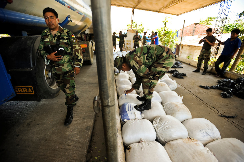 """Bolivian FELCN Special Forces count 75 bags of confiscated raw coca found during a raid, along with processing materials to convert it into cocaine-base in Villa Nuevo Horizonte, a dangerous area in the department of Santa Cruz were narcotraffiking runs rampant. FELCN officials report it is the area of Bolivia most thickly dense of narcotraffickers and cocaine-base processing laboratories.  FELCN police commonly referred to it as a """"narco pueblo""""."""