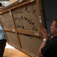 """Christie's exhibition space is transformed into an auction room for the evening sale. Workmen are carrying a painting by Spanish painter Miró: """"Femme à la voix de rossignol dans la nuit"""""""