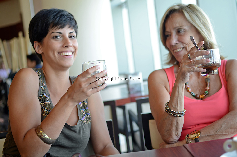 Young and mature woman have a drink and chat in a cafe