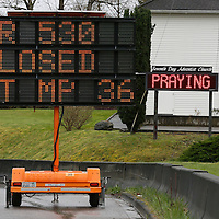 "A highway sign warns of the road closed by the mudslide while a sign on a church in the background reads ""keep praying"" in Arlington, Washington March 28, 2014.  Rescue officials said the death toll from a catastrophic mudslide in Washington state is soon expected to climb far higher, as some residents voiced anger that they were prevented from helping in the initial disaster response six days ago.   REUTERS/Rick Wilking (UNITED STATES)"